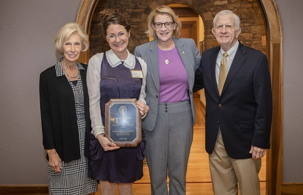 Dr. Martha McCaughey, director of Appalachian's First Year Seminar program and professor of sociology, second from left, holds the plaque she received as part of her 2019 Harvey R. Durham Freshman Advocate Award. Dr. Harvey Durham, for whom the award is named, far right, his wife, Susan Durham, far left, and Appalachian Chancellor Sheri Everts, second from right, presented McCaughey with the award after a breakfast held at the Appalachian House in April. Photo by Marie Freeman