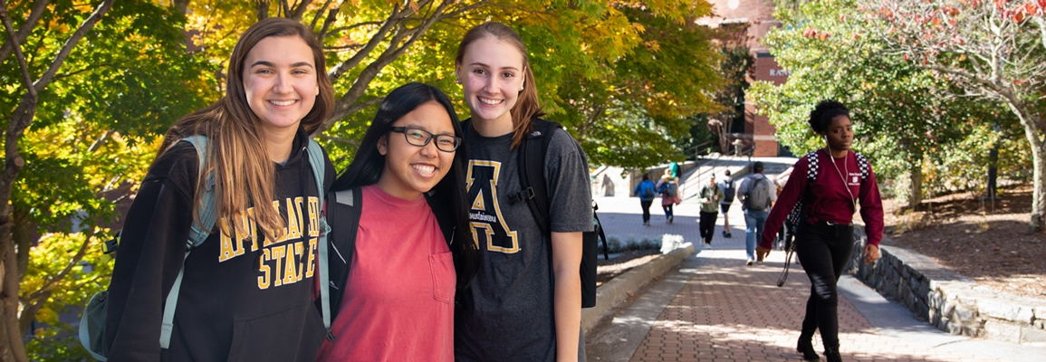 3 female students pose for a quick photo on campus during the fall semester