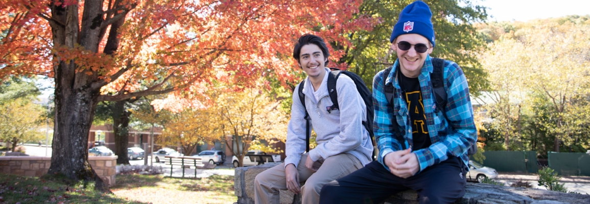 two male students sit on a rock wall, on campus with fall colors in the trees