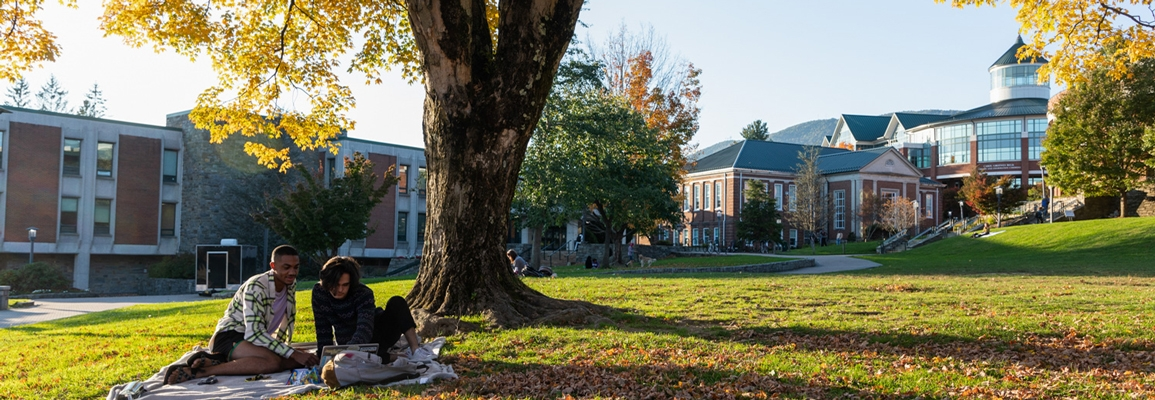 Campus life, students studying outside on Sanford Mall with Anne Belk Hall in the background. Anne Belk houses Anthropology, History, Computer Science and Government and Justice Studies.