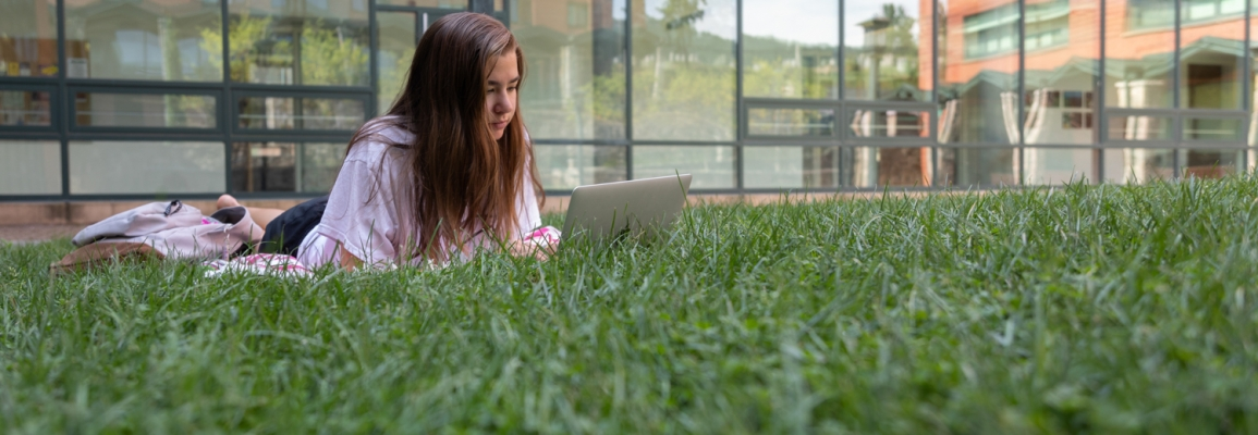 Campus Life, a student studying outside in the grass on App State's campus.