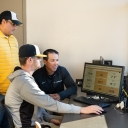 Dr. Rene Salinas, professor of Mathematical Sciences (left), with head coach of the baseball team, Kermit Smith and sophomore Cameron Lyons talk stats looking at Trackman data from the previous game. Photo by Ellen Gwin Burnette