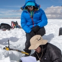 On top of the Quelccaya Ice Cap, junior geography major Cole Barrow, bottom right, relays measurements from a snow pit to senior geography major Michael Godwin, far left, and John Howarth, who played a supporting role during the expedition. Photo by Marie Freeman