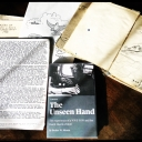 """The Unseen Hand"" book cover alongside Bealer Moore's sketchbook and memoir. Photo submitted."