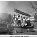 "A float in the 1953 homecoming parade celebrates ""50 years of progress."" Appalachian began as Watauga Academy in 1899 and then became the state-supported institution Appalachian Training School in 1903. The pictured 1953 homecoming float refers to Appalachian's 50th anniversary as a state-supported institution. In 1925, the university became Appalachian State Normal School; in 1929, it was named Appalachian State Teachers College; and in 1967, it became Appalachian State University, as it is known today. Ph"
