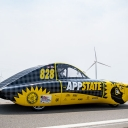 Solar-powered ROSE glides by a wind farm during the first leg of the 2021 American Solar Challenge. Photo by Kyla Willoughby