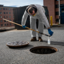 Eric Greer in Appalachian State University's Facilities Operations pours a wastewater sample from a university residence hall into a collection container. Photo by Marie Freeman