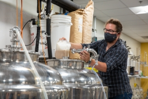 Daniel Parker, operations manager for the fermentation facility and lecturer in the Department of Chemistry and Fermentation Sciences, pitching the yeast into the fermentation tank. Photo by Ellen Gwin Burnette.