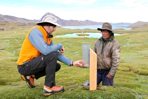 Baker Perry, left, shows Alpaca farmer Don Pedro Godfredo how to take precipitation measurements from his farm, located at an elevation of 16,700 feet near Peru's Quelccaya Ice Cap. Perry, an assistant professor of geography at Appalachian State University, has received a five-year National Science Foundation grant to expand his research of precipitation and climate change in the Andes Mountains in Peru and Bolivia. (Photo by Dr. Anton Seimon)