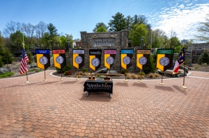 Displayed in front of the Appalachian State University sign, located in Founders Plaza on App State's campus, are the university mace and banner, along with the banners for App State's College of Arts and Sciences, Beaver College of Health Sciences, College of Fine and Applied Arts, Hayes School of Music, Reich College of Education, Walker College of Business and Cratis D. Williams School of Graduate Studies. The state flag is shown at far right and the U.S. flag is pictured at far left. Photo by Marie Free