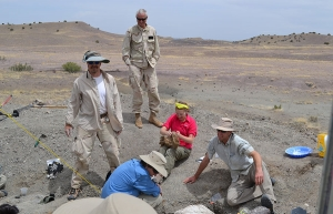 """Dr. Andy Heckert, far left, enjoys the progress his students are making on a 2014 dig in the Triassic of Arizona as part of his field course known as the """"Triassic Trip."""" Students seated on the ground are, from left to right, Devin Hoffman '17, now a Ph.D. candidate in geosciences at Virginia Tech; Chelsea Vaughn '16, a sergeant in the U.S. Army; and Mathew Sandefur '16, a geologist with the U.S. Department of Agriculture's Natural Resources Conservation Service. Standing in back is dig site volunteer Scott"""