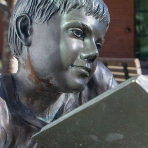 Pictured in fall 2019, an Appalachian State University student walks by an on-campus sculpture depicting a child mid-read. As part of App State's virtual spring 2021 Hughlene Bostian Frank Visiting Writers Series, three novelists from the Appalachian region — Charles Dodd White, Annette Saunooke Clapsaddle and Carter Sickels — will read from their work and give talks on the craft of writing, and playwright Anna Deavere Smith will give a storytelling presentation. Photo by Marie Freeman
