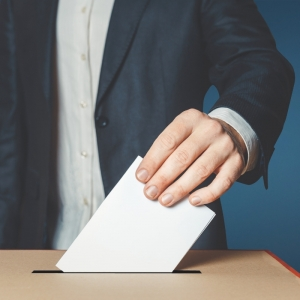 A hand placing a ballot in a box. Stock image.