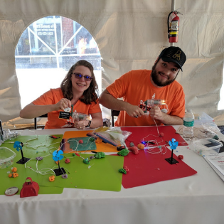 Dr. Leah Sherman, director of undergraduate laboratories, Department of Physics and Astronomy, and senior Trae Jenks showing squishy circuits at the PandA Booth at Gravity Games held in Lenoir, N.C. Photo submitted.